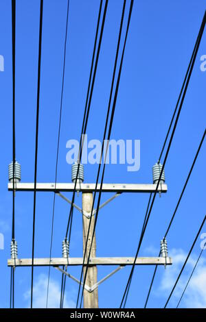Vertical view of electric grid wires going through isolators on top of pole. - Stock Photo