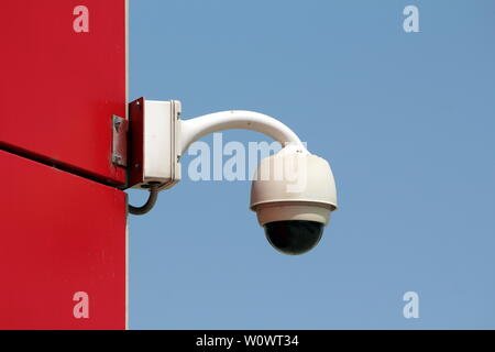 Ball shaped rotatable waterproof security camera CCTV mounted on side wall of red office building on warm sunny spring day - Stock Photo