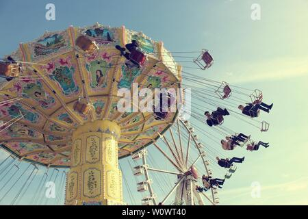 Editorial image of people having fun on wave swinger ride, vintage filter effect - Stock Photo