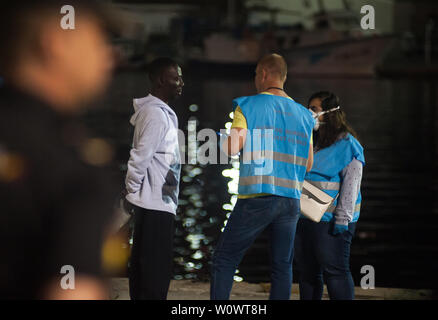 Malaga, Spain. 28th June, 2019. A migrant speaks with members of European Border and Coast Guard Agency (Frontex) outside a tent of the Spanish Red Cross after their arrival at the Port of Malaga.Spain's Maritime Rescue service rescued 50 migrants aboard a dinghy crossing the Alboran Sea and brought them to Malaga harbor, where they were assisted by the Spanish Red Cross. Credit: SOPA Images Limited/Alamy Live News - Stock Photo
