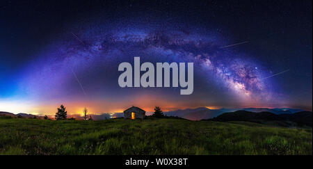 Make a wish - Meteor shower during summer with full arc of milky way. Beautiful Universe. Small chapel in foreground. Space background. - Stock Photo