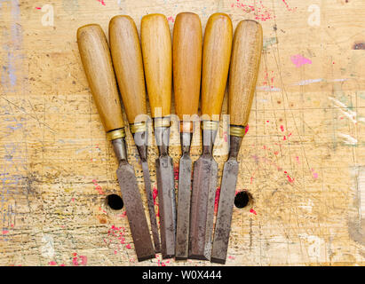 Group of assorted woodworking chisels isolated on wooden bench grunge surface. - Stock Photo