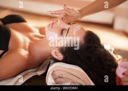 Spa. Beautiful woman relaxing during rejuvenating facial massage in a modern beauty center - Stock Photo