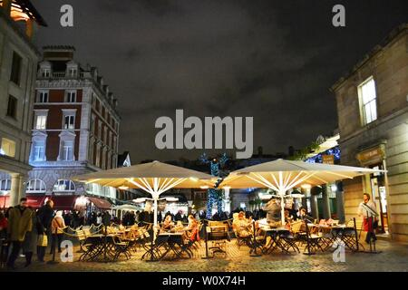 London/UK - November 27, 2013: People eating under tents at the Covent Garden external catering space during Christmas holidays. - Stock Photo