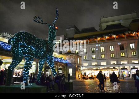 London/UK - November 27, 2013: Covent Garden square by night decorated for Christmas with giant topiary illuminated with LED lights reindeer by night. - Stock Photo