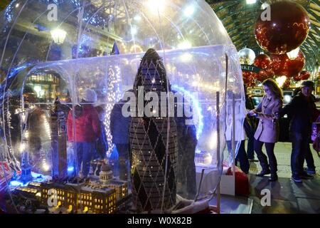 London/UK - November 27, 2013: People enjoying models of London famous landmarks exposed in the Covent Garden Apple market decorated for Christmas. - Stock Photo