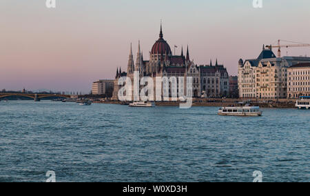 Tour boats on the Danube River near the Hungarian Parliament Building in Budapest, Hungary at sunset. - Stock Photo