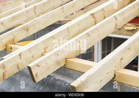 Timber roofing trusses or joists on a new house during construction - Stock Photo