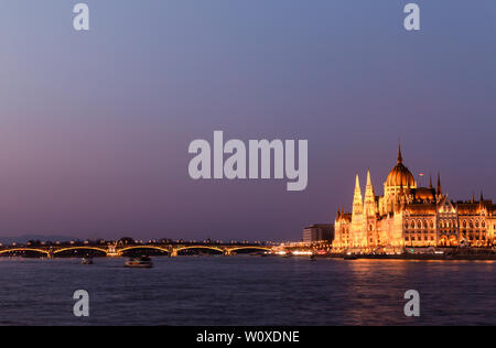 Tour boats on the Danube River in front of the Hungarian Parliament Building in Budapest, Hungary at twilight. Motion blur. - Stock Photo