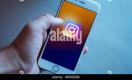 New York / Usa 06-27-2019: Man is holding a white smartphone with the icon of the instagram social network represented. - Stock Photo