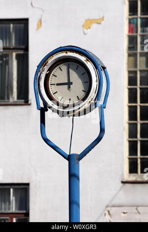 Outdoor analog clock with rusted metal frame in middle of abandoned industrial complex with old dilapidated building in background - Stock Photo