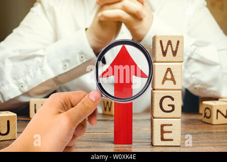 Red arrow up near wooden blocks with the word Wage and a businessman. Salary increase concept. Wages rate. Revenue growth and profits. Successful busi - Stock Photo