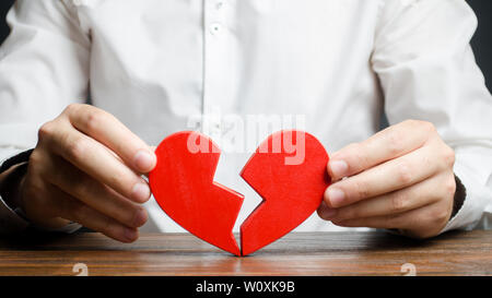 A man collects a broken heart in his hands. Concept of love and relationships. Family psychotherapist services. Reconciliation. Saving the family. Sea - Stock Photo
