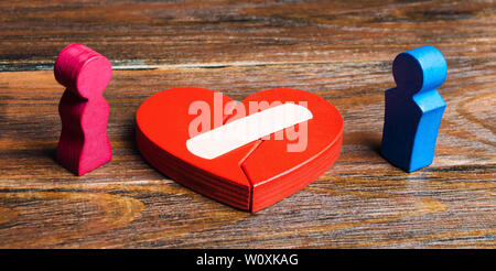 A red heart with a plaster and couple in lovers. Renewal of the relationship. Family psychotherapist services. Reconciliation. Saving the family. Sear - Stock Photo