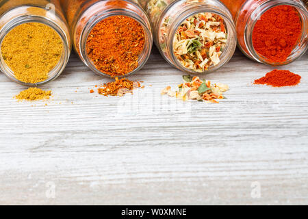 Spices pouring out of jars lying on a wooden countertop