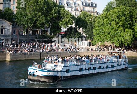 Paris, France. 27th June, 2019. People rest at the riverside of Seine in Paris, France, June 27, 2019. The national weather center, Meteo France, on Thursday warned of 'exceptional heat peak' on June 28, placing 4 southern regions on red alert, the highest alert on the agency's four-scale system, and urges residents to be extremely vigilant. While 76 other regions, except Brittany, in northwest France, remain on orange alert till next week. Credit: Jack Chan/Xinhua/Alamy Live News - Stock Photo
