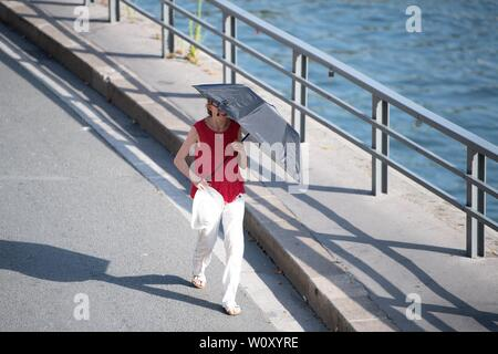 Paris, France. 27th June, 2019. A woman walks with a sunshade in Paris, France, June 27, 2019. The national weather center, Meteo France, on Thursday warned of 'exceptional heat peak' on June 28, placing 4 southern regions on red alert, the highest alert on the agency's four-scale system, and urges residents to be extremely vigilant. While 76 other regions, except Brittany, in northwest France, remain on orange alert till next week. Credit: Jack Chan/Xinhua/Alamy Live News - Stock Photo