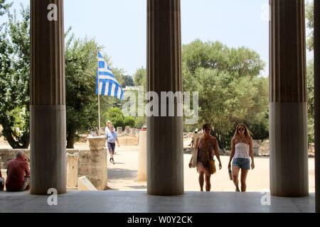 Ancient Agora of Athens two women near pillars and greek flag greece - Stock Photo