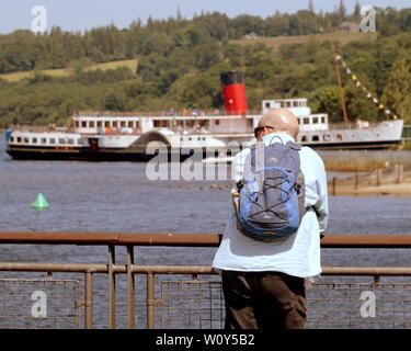 Glasgow, Scotland, UK 28th June, 2019. UK Weather: Saharan heatwave hit Loch Lomond as it  saw a scorcher as finally the prospect of a summer materialised. Tourists admire PS Maid of the Loch is the last paddle steamer built in Britain. She operated on Loch Lomond for 29 years and as of 2019 is being restored at Balloch pier.  Credit: Gerard Ferry/ Alamy Live News - Stock Photo