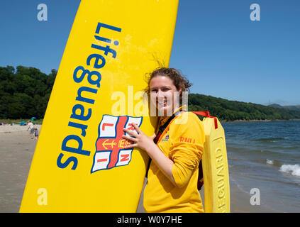 Aberdour, Fife, Scotland, UK. 28 June, 2019. Lifeguard Anna Whyte from Kinghorn in Fife was kept busy at Silver Sands Beach at Aberdour as warm weather and sunshine attracted dozens of people to the seaside. When she is not on duty as a lifeguard , Anna is also a volunteer with the local RNLI lifeboat. Credit: Iain Masterton/Alamy Live News - Stock Photo