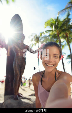 Waikiki Beach Tourist in Honolulu on Oahu, Hawaii taking selfie self portrait photograph in front of famous tourist attraction and surfing landmark, the statue of Duke Kahanamoku. Travel on Hawaii. - Stock Photo