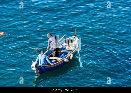 RIOMAGGIORE, ITALY - JAN 2, 2015: Two fishermen on a small wooden boat are coming out to fish from the small port of Riomaggiore, Cinque Terre, Liguri - Stock Photo