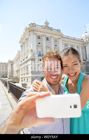 Couple taking selfie photo on smartphone in Madrid. Romantic man and woman in love using smart phone to take self-portrait photograph on travel in Madrid, Spain. - Stock Photo