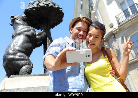 Tourists taking selfie photo pictures by famous bear statue Madrid on Puerta del Sol. Young couple using smartphone camera at tourist attraction Bear and the Madrono Tree, symbol of Madrid, Spain. - Stock Photo