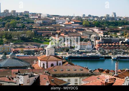 A view of the port wine lodges on Vila Nova de Gaia side of River Douro,  tourist ships & roofs of Ribeira Porto Oporto Portugal   KATHY DEWITT - Stock Photo