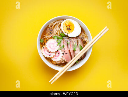 Tasty Japanese noodle soup ramen in white ceramic bowl with meat broth, sliced pork, narutomaki, egg with yolk on pastel yellow background. Traditiona - Stock Photo