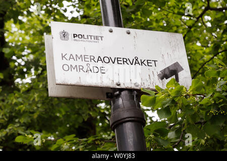 Oslo, Norway - June 20, 2019: Sign in Norwegian with information near the National thatre are camera-monitored area by the police department. - Stock Photo