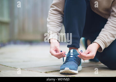 Millennial young man in dark blue jogging pants and a light brown hoodie, kneeling and tying his shoe laces on the ground in a backyard before jogging - Stock Photo