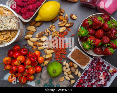 Healthy food clean eating selection: seeds, superfoods, vegetables and fruits powder on gray concrete background, close up - Stock Photo