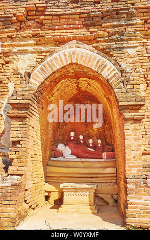 The small niche in ancient pagoda with statue of Reclining Buddha and disciples around him, Bagan, Myanmar - Stock Photo
