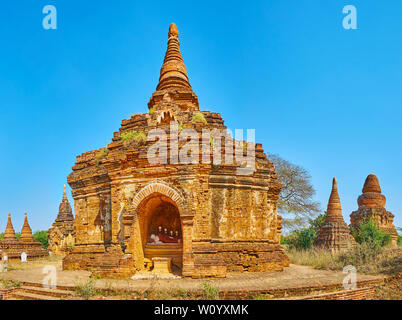 Panorama of the ancient brick shrine, decorated with carved patterns and image of Reclining Buddha, Bagan, Myanmar - Stock Photo