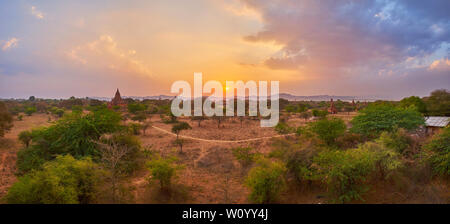 Panorama of savannah, covering the plain of Bagan with green trees, dry soil, stupas and temples of archaeological site and mountains on background, M - Stock Photo