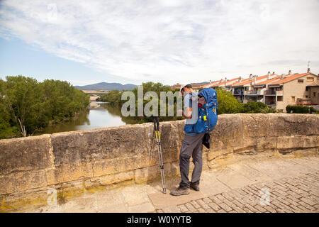 Man Pilgrim walking over the medieval bridge in the town of Puente la Reina while walking the Camino de Santiago  pilgrimage route Spain - Stock Photo