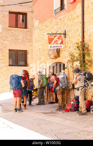 Pilgrims men  woman  walking the Camino de Santiago the way of St James stopped outside the Albergue at the village of Lorca Northern Spain - Stock Photo