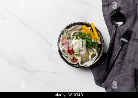 Asian soup with noodle, meat and vegetables in bowl with napkin and tableware on white background. Horizontal top view, free space for text - Stock Photo