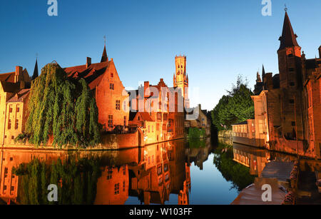Famous view of Bruges tourist landmark attraction - Rozenhoedkaai canal with Belfry and old houses along canal with tree in the night. Bruges, Belgium