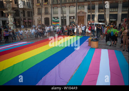 People gather around a large pride flag during a demonstration to celebrate the International Pride LGTBI Day 2019, organized by Andalusia Rainbow Federation.Thousands of people around the world take part on the Pride LGTBI, marked the anniversary of 50 years of Stonewall riot which commemorated the fight of gays, lesbians, transgender, bisexuals and intersexual during the first demonstrations in US in favour of their rights. - Stock Photo