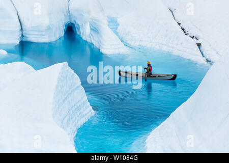 Man on a canoe floats above a flooded ice cave in a deep blue pool while being rained on in Alaska - Stock Photo