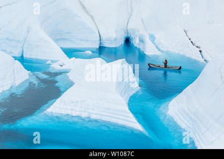 On the Matanuska Glacier in Alaska, an ice climbing guide floats an inflatable canoe on a deep blue lake on the glacier. The narrow flooded canyons le - Stock Photo