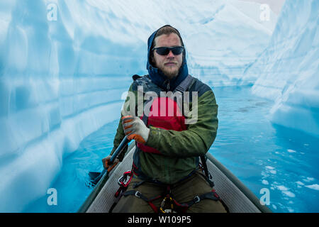Ice climber focused on paddling through a narrow ice canyon on top of the Matanuska Glacier in Alaska. - Stock Photo