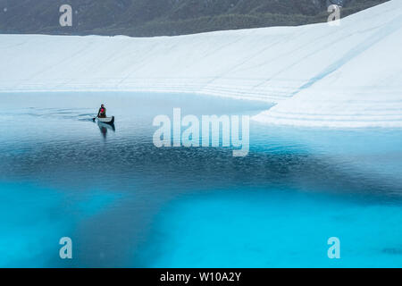 Paddling across a supraglacial lake on the Matanuska Glacier in the rain. Ice climber corssing a deep blue lake getting rained on. - Stock Photo