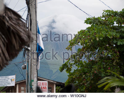 Behind Moyogalpa, the main landing port on Ometepe  Island  is Volcan Concepcion, a still active volcano whose last eruption was in 2015. - Stock Photo
