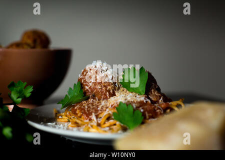 A close-up shot of a plate of rustic spaghetti and meatballs with a bowl of meatballs, parmesean cheese, and fresh parsley - Stock Photo