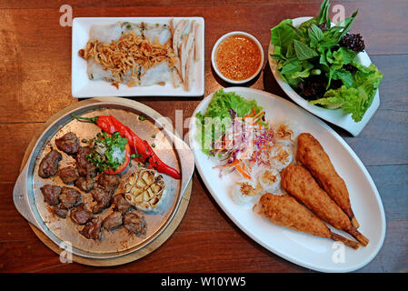 Top view of popular Vietnamese dishes on the wooden table - Stock Photo