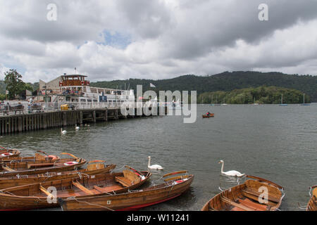 Rowing boats for hire  on the shore of Lake Windermere at Bowness upon Windermere with some swans and a trip boat in the background - Stock Photo