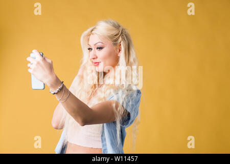 Lovely caucasian student with cute smile, looking at camera of cell phone, making video call to her best friend or mother, dressed in casual clothes, - Stock Photo